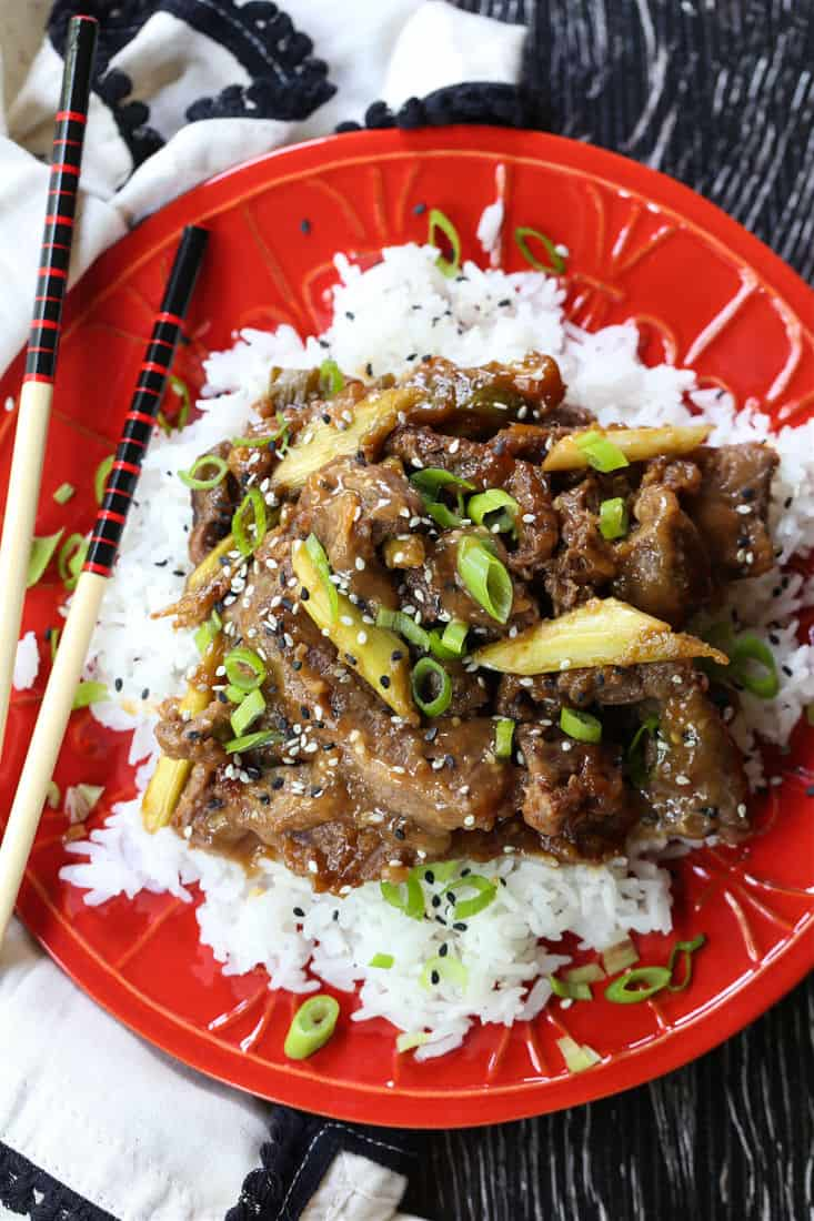 Slow Cooker Mongolian Beef on a red p ate with rice
