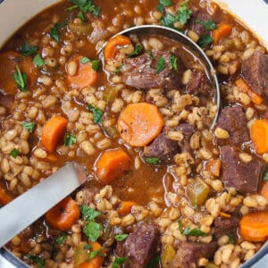 Beef Barely Soup in a pot with a ladle