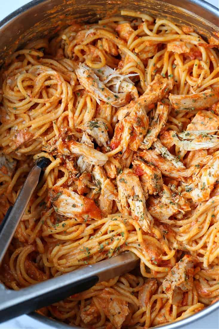 Chicken spaghetti recipe being tossed in a pot