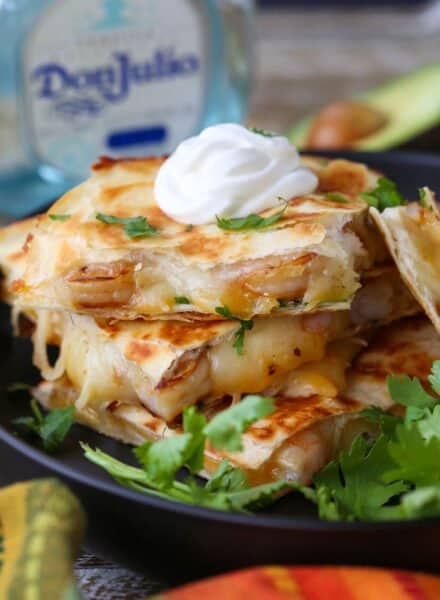 Tequila Shrimp Quesadillas stacked on a plate with tequila bottle